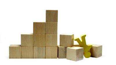 A pile of wooden blocks with a person shaped block falling down