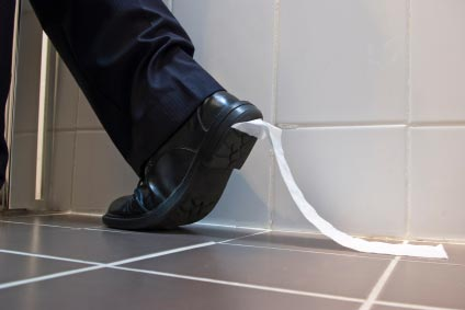 Toilet paper stuck to a foot