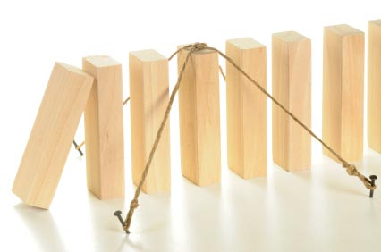 A row of dominoes, the fourth domino is tied in a fashion that will not allow it to tip over