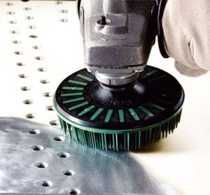 A bristle disc running on a right angle grinder removes paint from a metallic surface