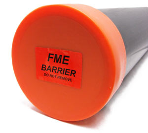 An orange npt cover with a sticker identifying it as an FME barrier