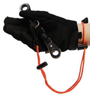 A rope style wrist lanyard is attached to a gloved hand holding a tool